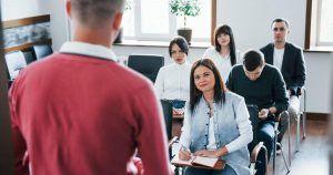 Un instructor ofrece una clase frente a un grupo de alumnos, que son jóvenes profesionales y se encuentran muy atentos