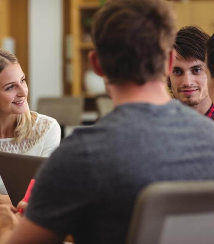Un grupo de colaboradores tiene una reunión de trabajo dentro de una oficina.