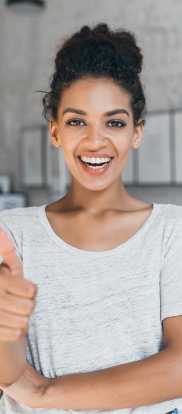 Una joven mujer afroamericana sube su pulgar como expresión de alegría y aprobación