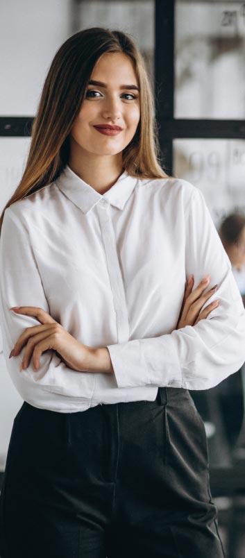 Una joven ejecutiva, en su oficina, sonríe y se siente feliz porque cuenta con herramientas de Coaching Ontológico