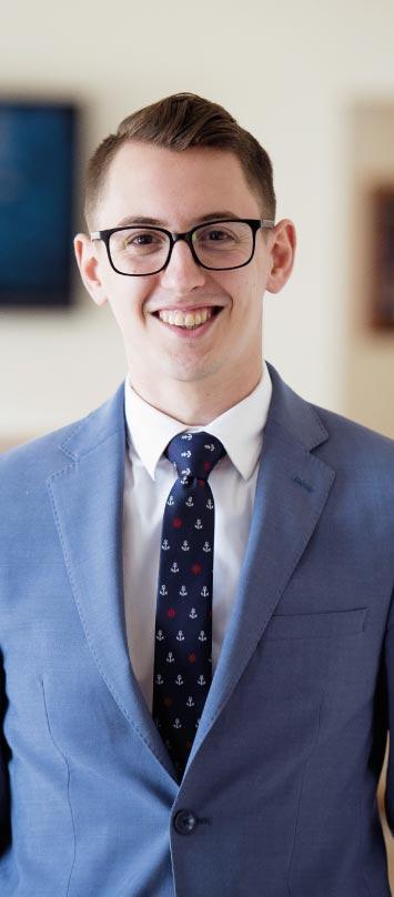 Un joven ejecutivo con traje sonríe y se siente feliz porque cuenta con herramientas de Coaching Ontológico