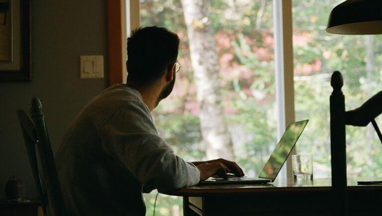 Un hombre está en el escritorio de su casa de campo trabajando sobre la nueva realidad linguística