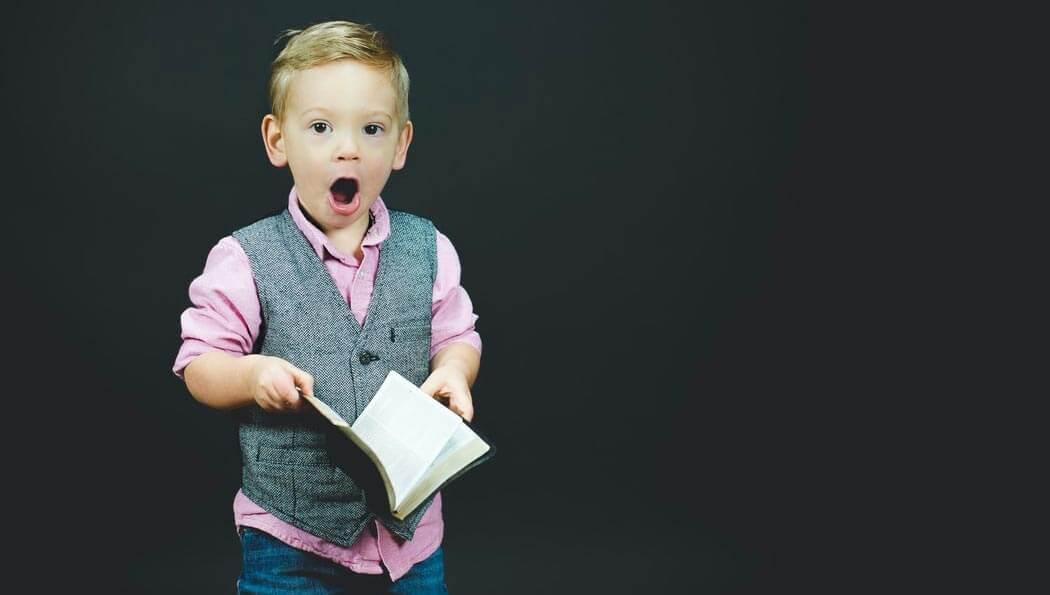 Niño sorprendido toma un libro. Internalizó el poder de las preguntas, como parte del coaching ontológico